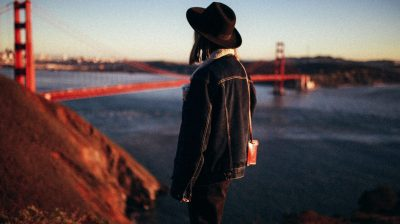 Photo of a person wearing a hat and staring at the Golden Gate Bridge in the distance