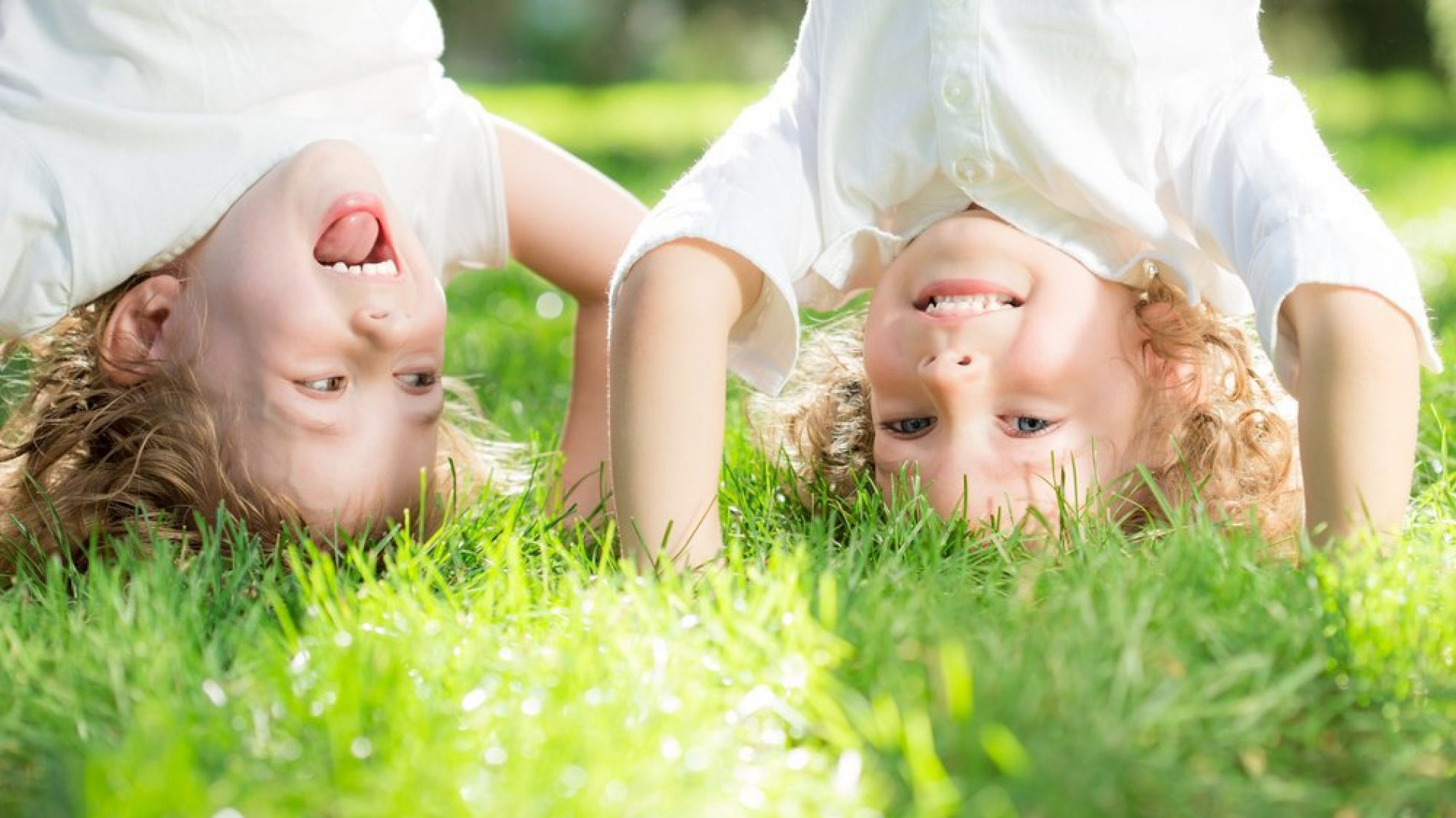 Two kinds doing head stands on grass