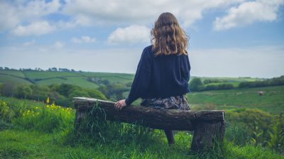 Young woman on bench in countryside