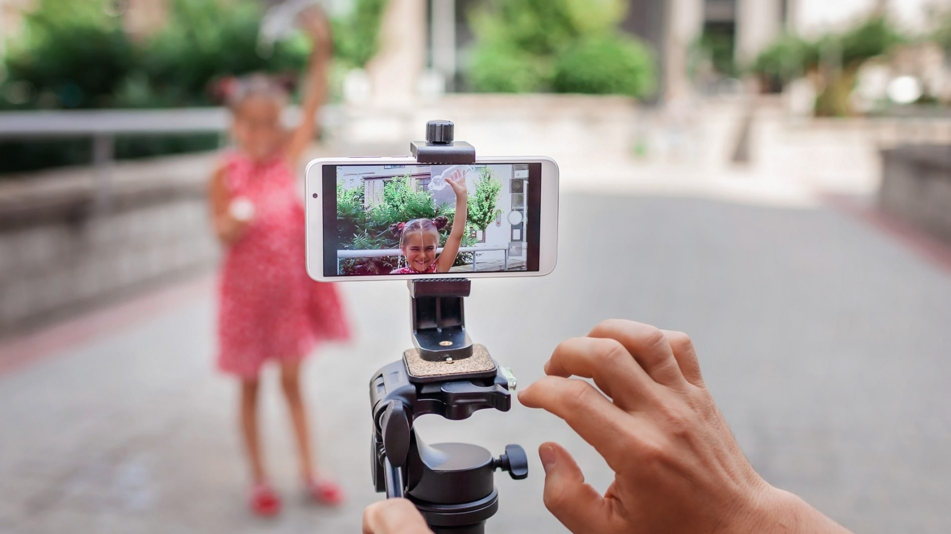 A person recording footage on their phone of a young girl