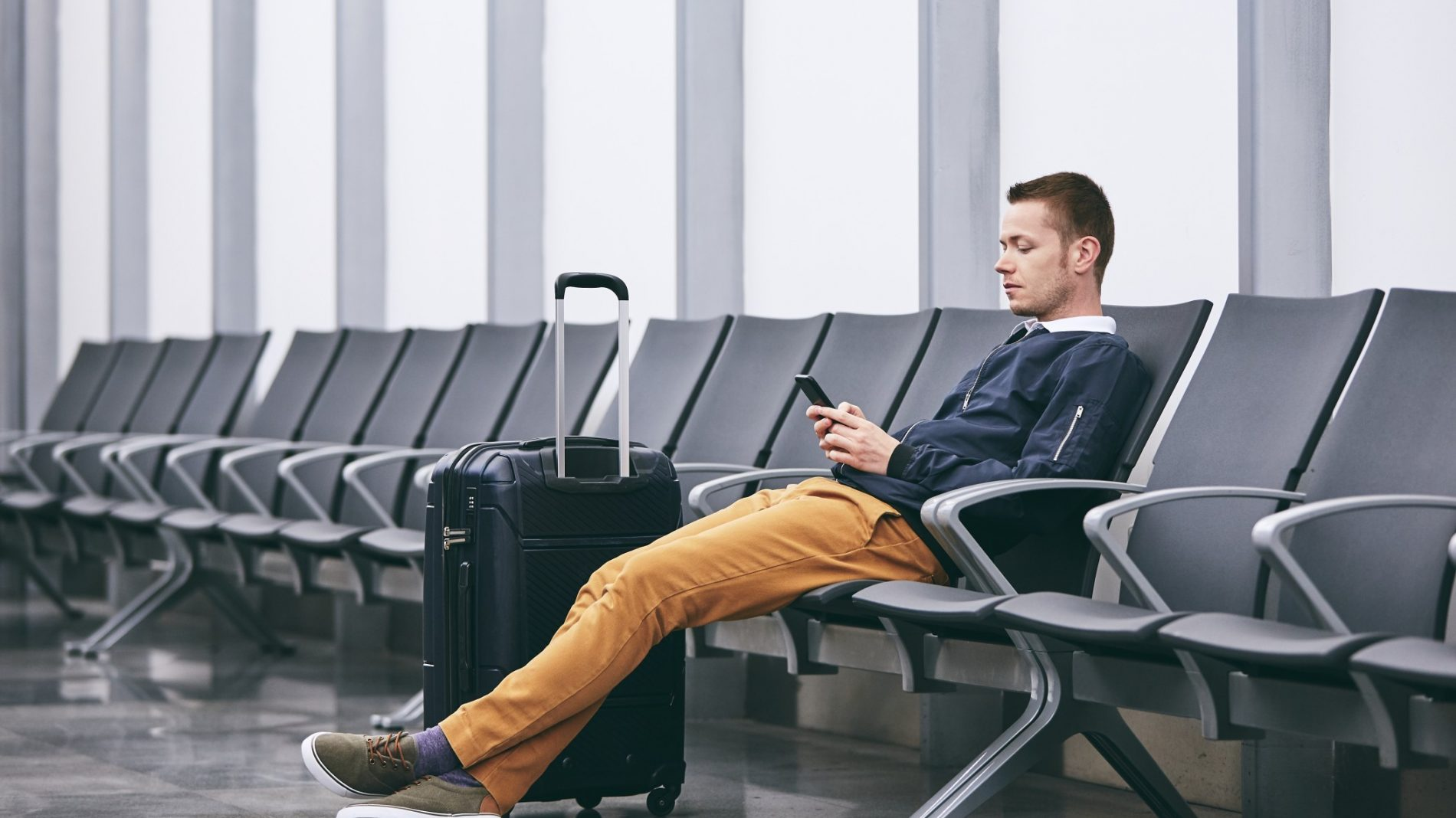 man-traveling-by-airplane-young-passenger-using-phone-waiting-in-airport-terminal_t20_W7B7Y4