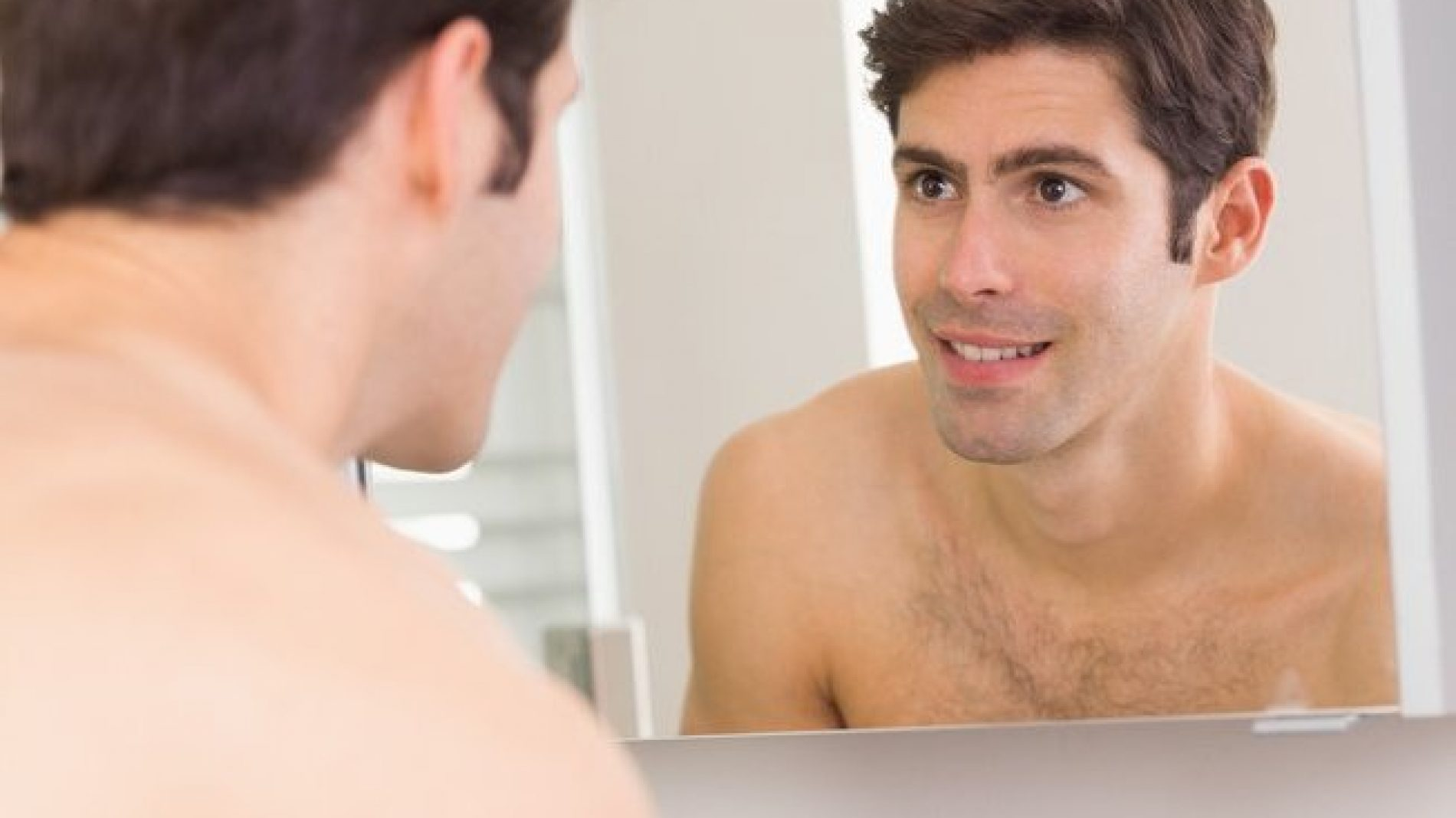 A shirtless man looking in the mirror