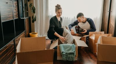 Photo of two people sitting on floor while packing cardboard boxes