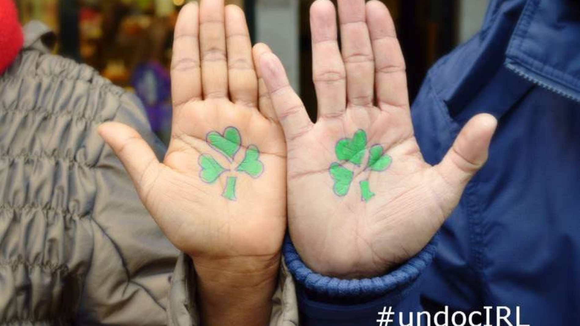 Two hands with shamrocks printed on them