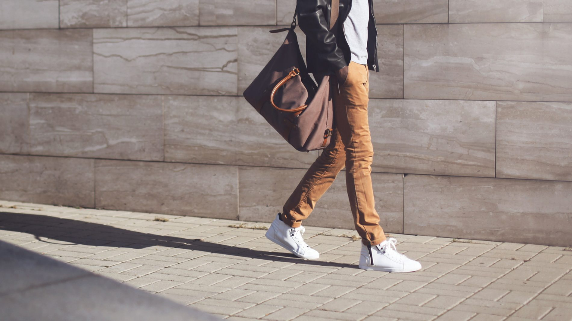 Fashion african man in black jacket walking in city