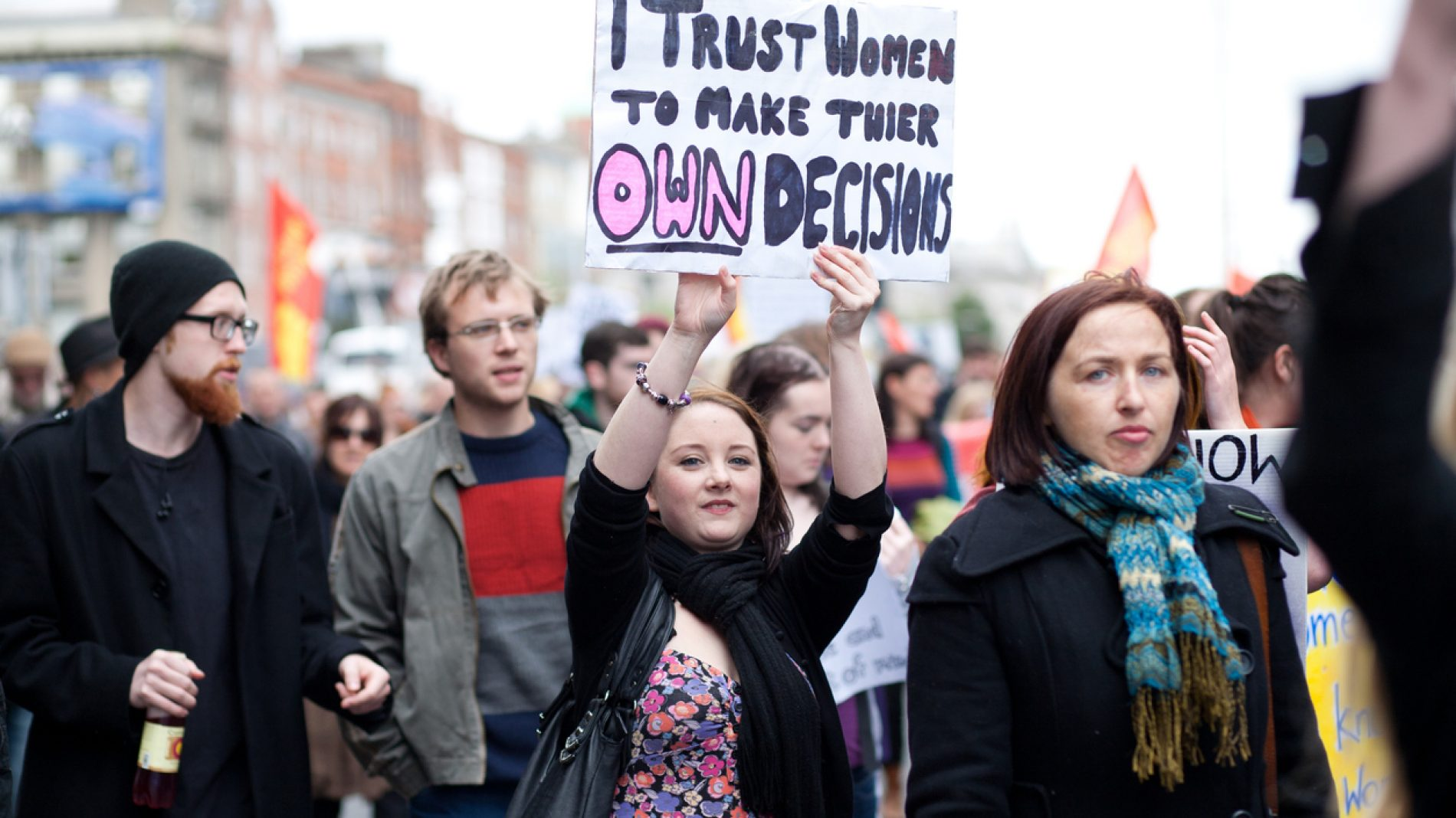 Young woman holds hand made poster about women decisions