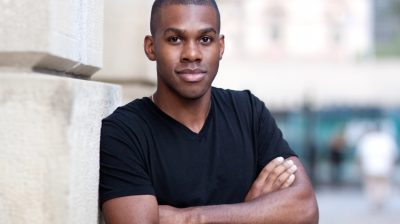 A young Black person leaning against a wall
