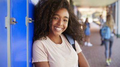 Portrait of black teenage girl by lockers in school corridor