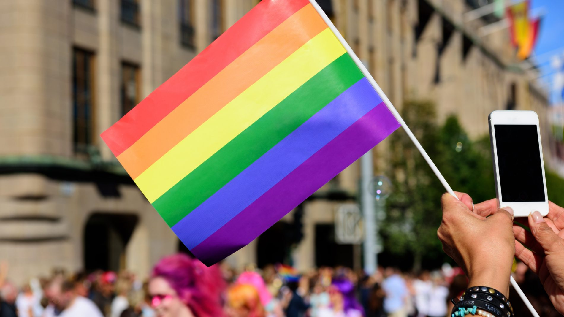 Someone holding pride colour flag with people in the background