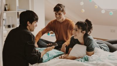 Photo of three young people sitting on a bed while talking
