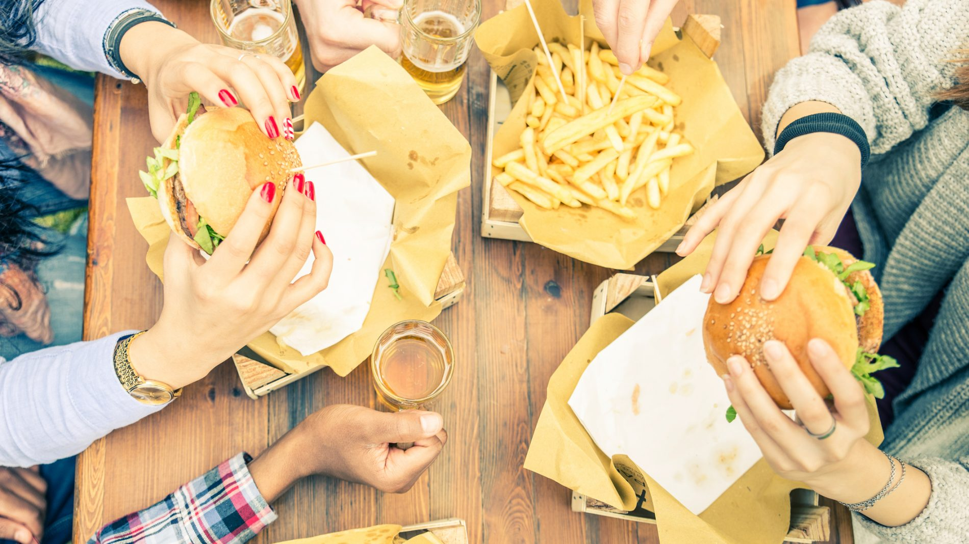 Picture of people sitting at table eating burgers