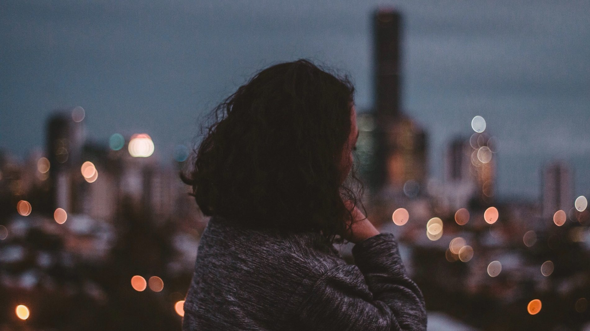 A young woman looking into the distance in front of a city skyline