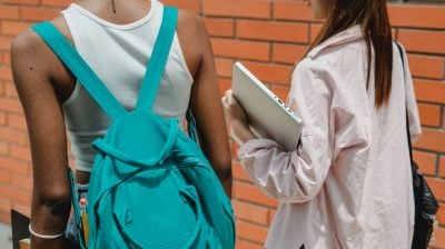 two people walk side by side, one holds a laptop and the other is carrying a backpack - sexual violence
