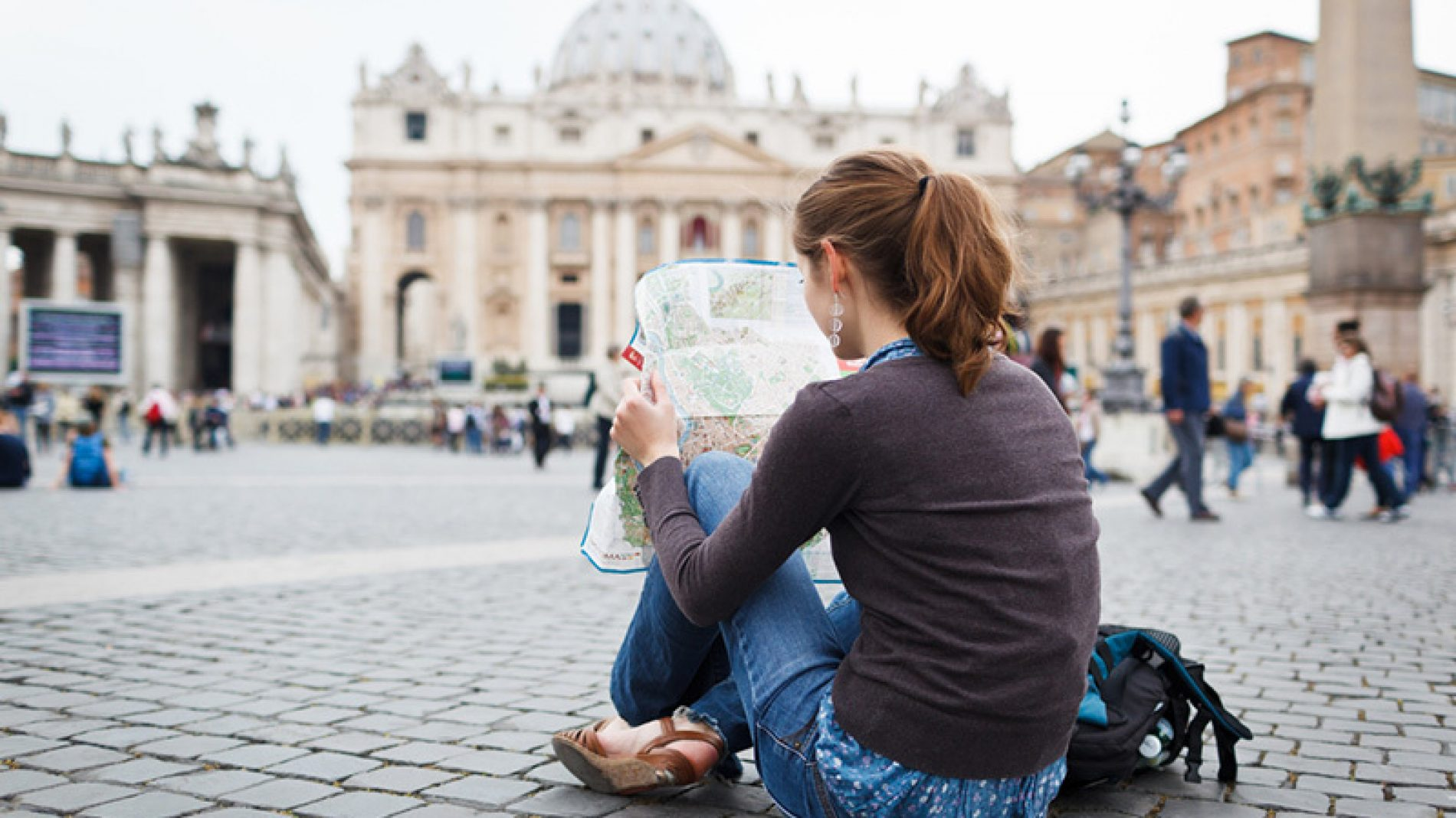 Photo of a person sitting on the ground in a city looking at a map