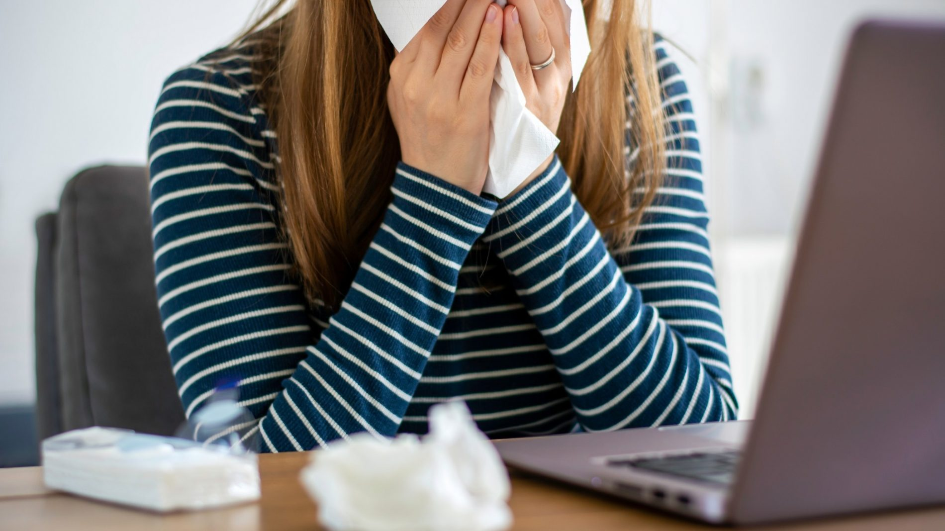 sick-woman-working-on-laptop-at-home-covering-nose-and-mouth-when-coughing-and-sneezing-in-tissue-ill_t20_WgkLQK