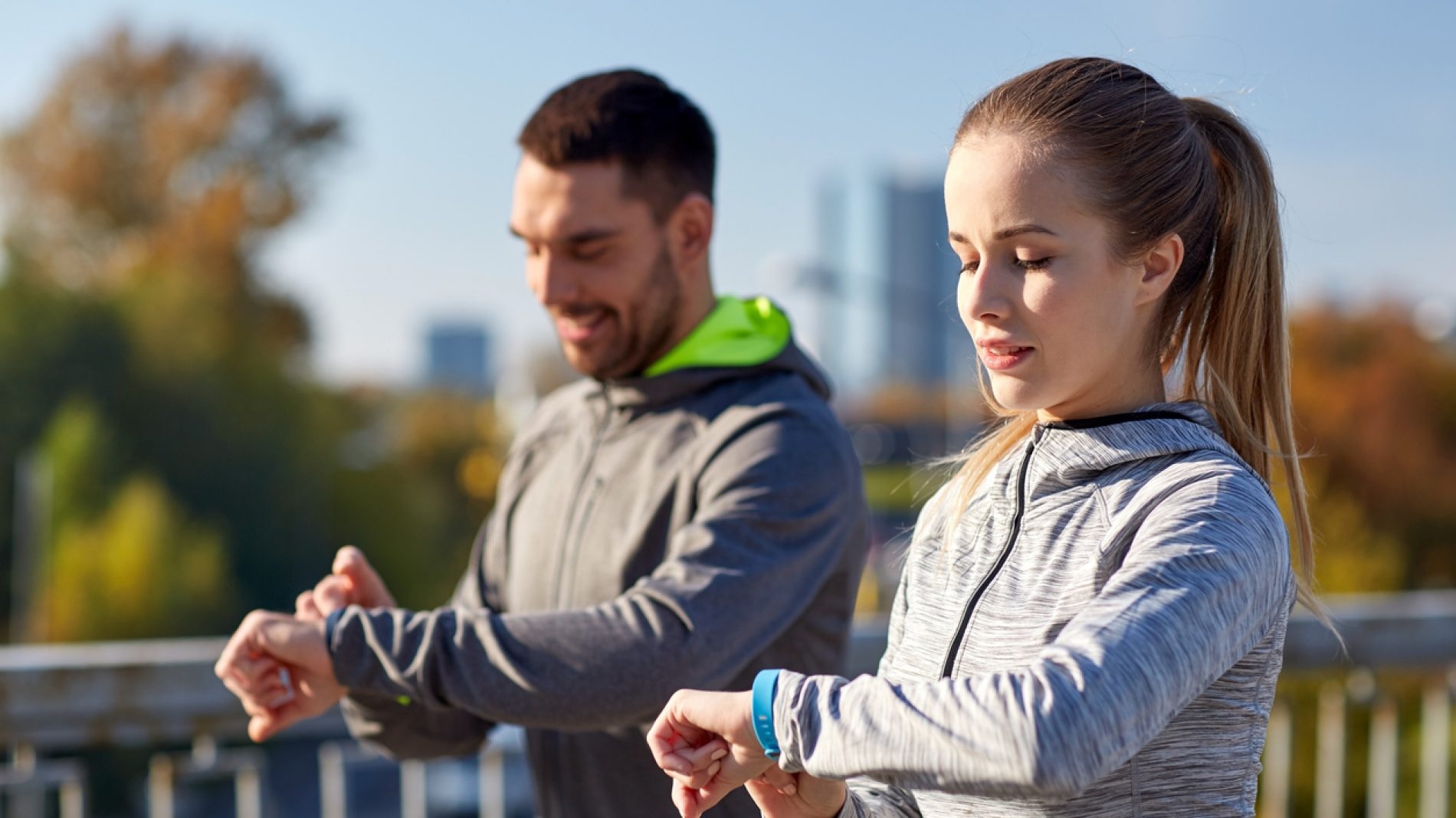 couple with fitness trackers training in city