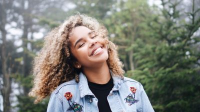 Happy smiling woman with curly hair wearing jean jacket spunout impact video