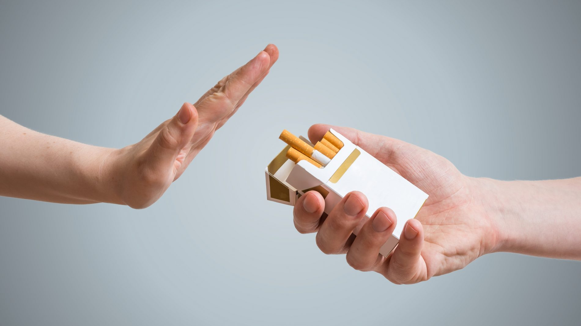 A packet of cigarettes and a hand pushing them away