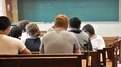 Young people looking at a black board in a class room