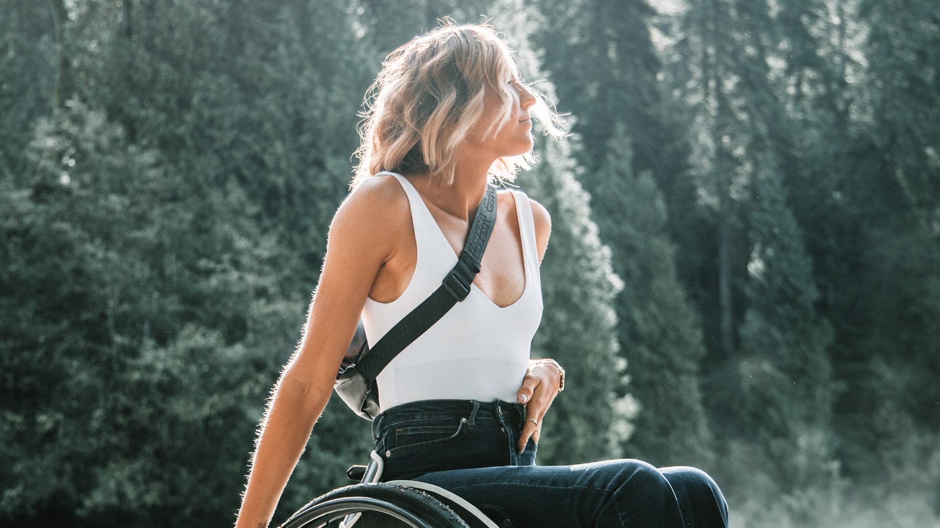 feminine person riding a wheelchair looking hopeful at the edge of a forest support PTSD