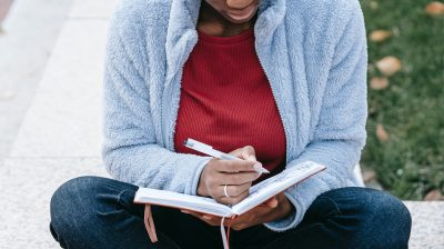 person sits cross legged writing into a journal anxiety depression