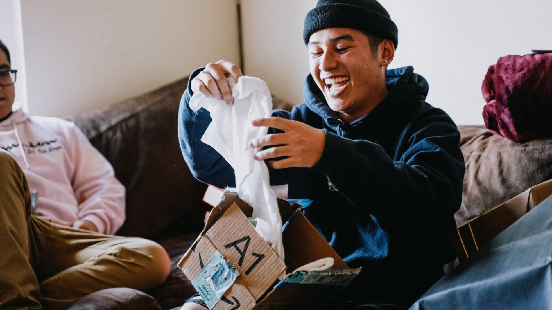 Photo of a person smiling while opening a present