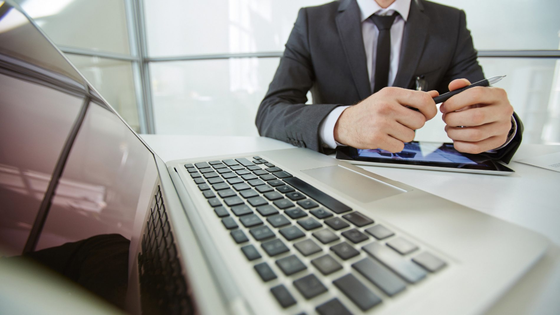 Close-up of laptop and businessman sitting at the table behind
