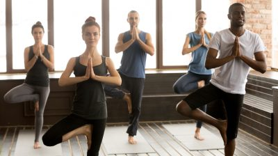 Group of sporty people in Vrksasana pose, close up
