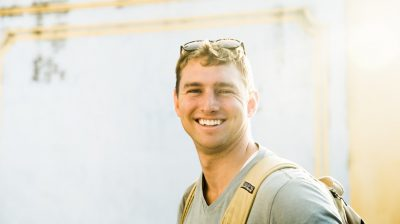 Young man smiling outside in the sun