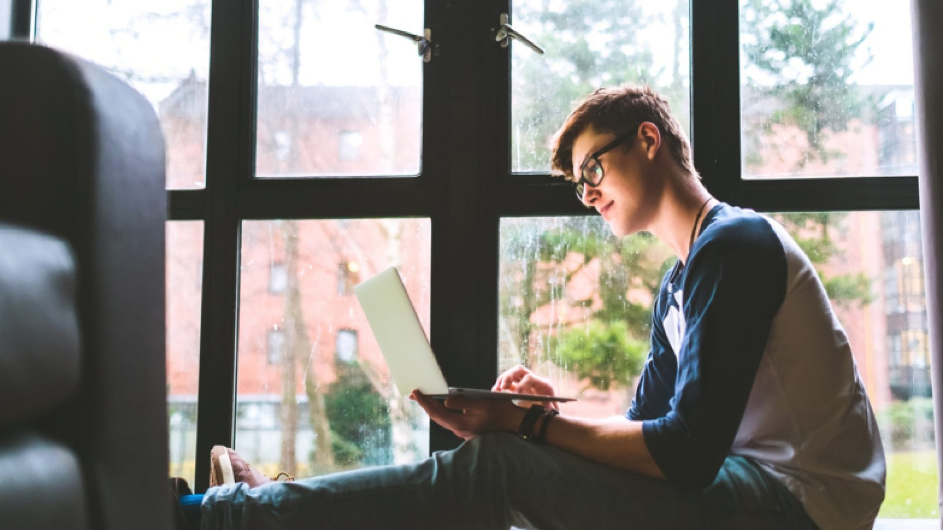 young-man-on-laptop-at-the-window-WWVmdt