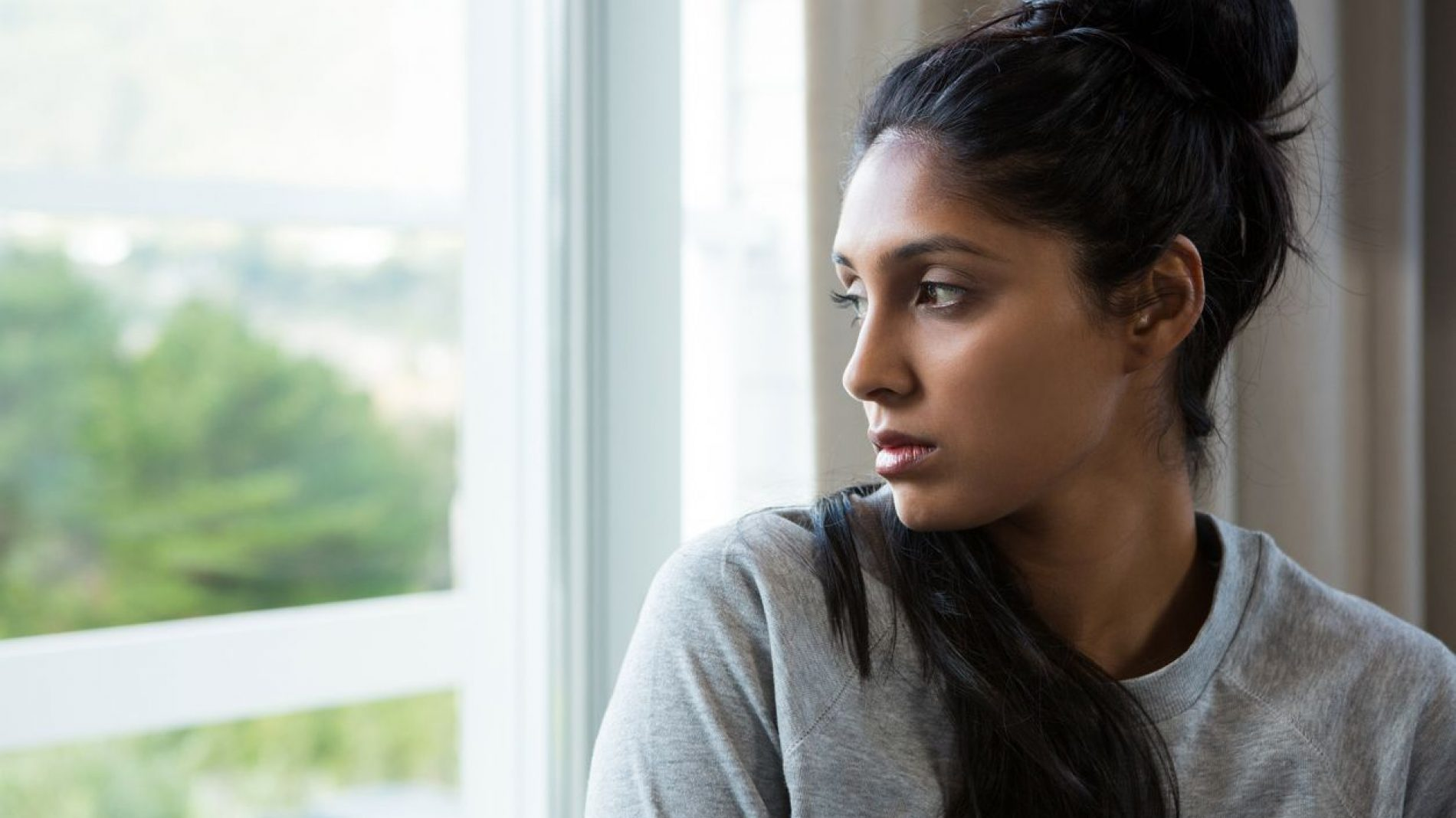 young-woman-by-window-thinking