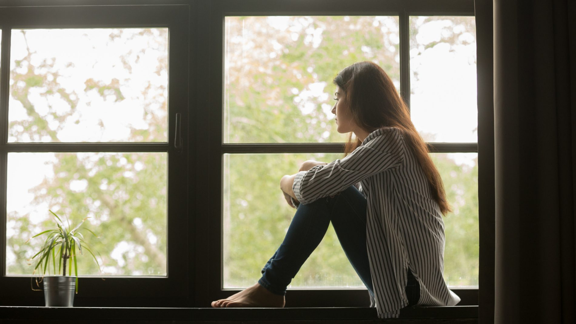 Young woman looking out the window.