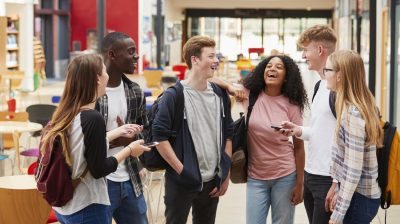 A group of 6 young people chatting and laughing together