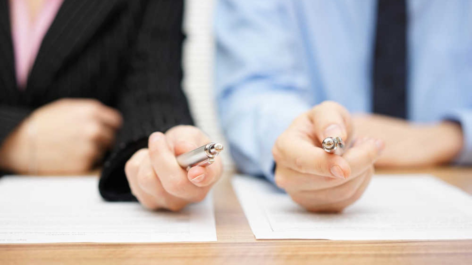 Two agents giving his client a pen to sign a deal